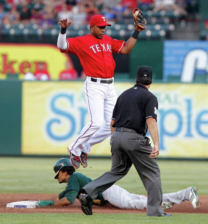 Oakland Athletics' Coco Crisp slides under Texas Rangers shortstop Elvis Andrus as he steals second base, while umpire Phil Cuzzi watches during the third inning of a baseball game Thursday, June 28, 2012, in Arlington, Texas. Photo: AP