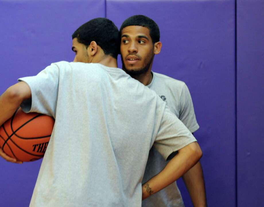"""Talor Battle, greets Davante Buie, 19, left, during the Talor Battle Basketball Camp, sponsored by All Basketball Inc., at Troy High School on Thursday June 28, 2012 in Troy, NY.  """"He's my blood brother,"""" said Buie of Battle, adding that they spent a lot of time together when they were growing up. (Philip Kamrass / Times Union) Photo: Philip Kamrass / 00018282A"""