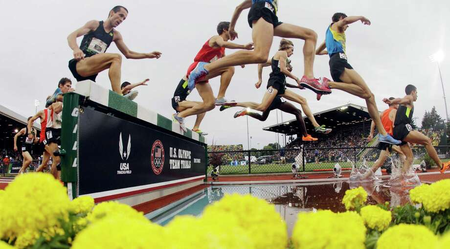 Competitors take the water jump in the men's 3000 meter steeplechase final at the U.S. Olympic Track and Field Trials Thursday, June 28, 2012, in Eugene, Ore. Evan Jager, wearing 13 on his leg, won the race. Photo: Charlie Riedel, Associated Press / AP