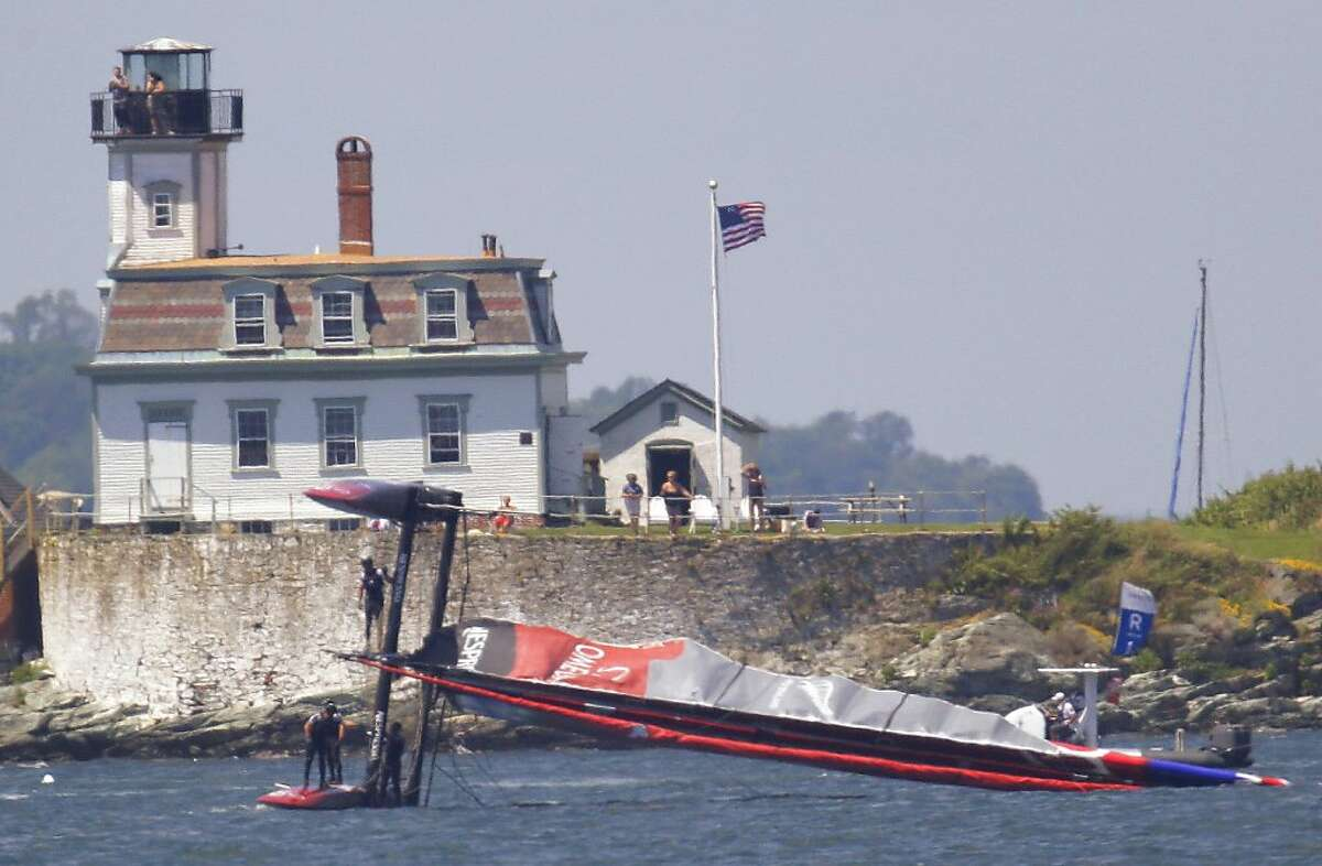 Team New Zealand crew members hang on as they attempt to right their ship after their boat capsized during a match race at the first day of the America's Cup World Series regatta in Newport, RI., Thursday, June 28, 2012. (AP Photo/Stephan Savoia)