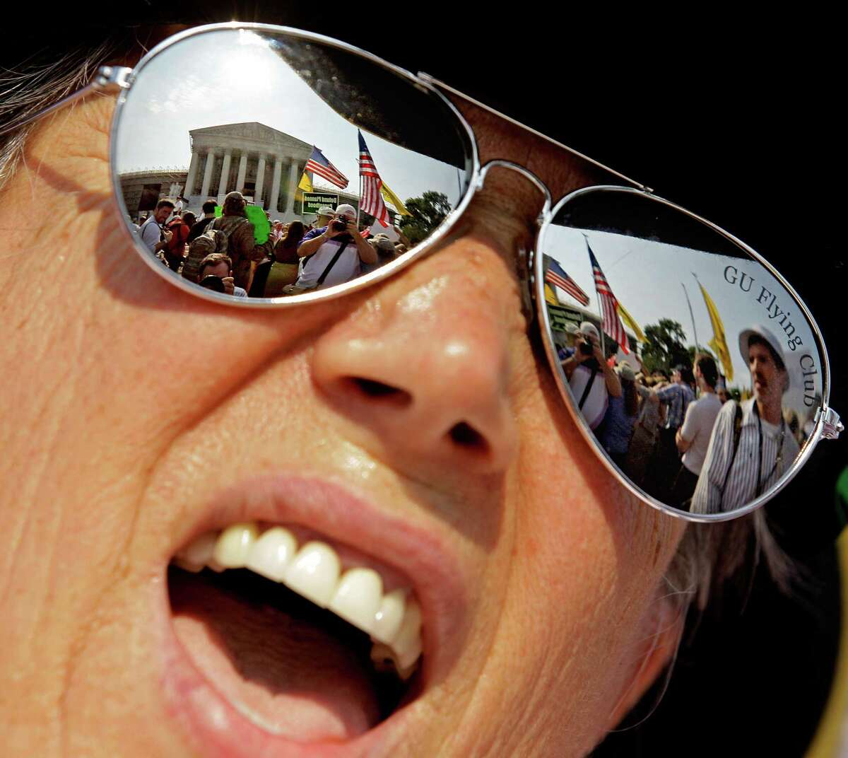 The Supreme Court is reflected in the sunglasses of Susan Clark, of Washington, as she demonstrates against President Barack Obama's health care law while awaiting the court's ruling, Thursday, June 28, 2012, in Washington. (AP Photo/David Goldman)