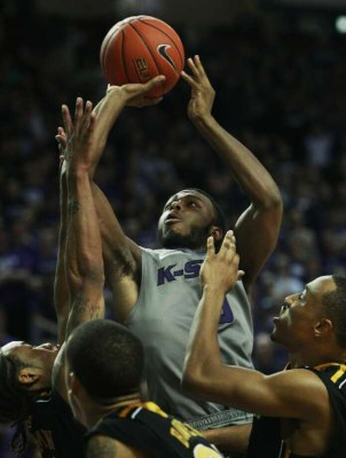 Kansas State guard Jacob Pullen (0) shoots over Missouri defenders Marcus Denmon, left,  Laurence Bowers and Matt Pressey, right, during the second half of an NCAA college basketball game Saturday, Feb. 26, 2011, in Manhattan, Kan. Pullen scored 24 points in the game. Kansas State defeated Missouri 80-70. (AP Photo/Orlin Wagner) (AP)