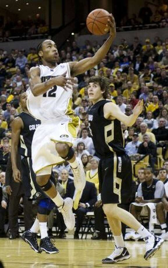 Missouri's Marcus Denmon, left, shoots past Colorado's Keegan Hornbuckle, right, while scoring two of his game-high 21 points during the second half of an NCAA college basketball game Wednesday, Feb. 24, 2010, in Columbia, Mo. Missouri won the game 92-63. (AP Photo/L.G. Patterson) (AP)