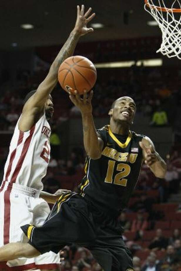 Missouri guard Marcus Denmon (12) goes to the basket in front of Oklahoma's Cameron Clark (21) during the first half of an NCAA college basketball game in Norman, Okla. on Monday, Feb. 6, 2012.  Missouri won 71-68.  (AP Photo/Alonzo Adams) (ASSOCIATED PRESS)