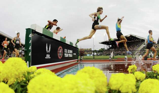 Competitors take the water jump in the men's 3000 meter steeplechase final at the U.S. Olympic Track and Field Trials Thursday, June 28, 2012, in Eugene, Ore. Evan Jager, wearing 13 on his leg, won the race.  (AP Photo/Charlie Riedel) Photo: Associated Press