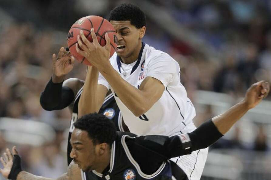 Connecticut forward Jeremy Lamb, top, grabs a loose ball away from Butler guard Shawn Vanzant uring