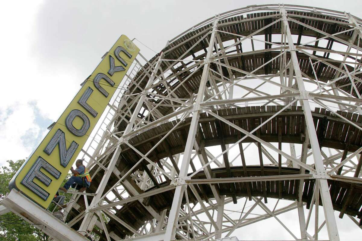 In a Tuesday, June 26, 2012 photo made at Coney Island in New York, a maintenance worker inspects the Cyclone roller coaster sign. The New York City landmark and international amusement icon will be feted Saturday, June 30 with a birthday party in its honor.