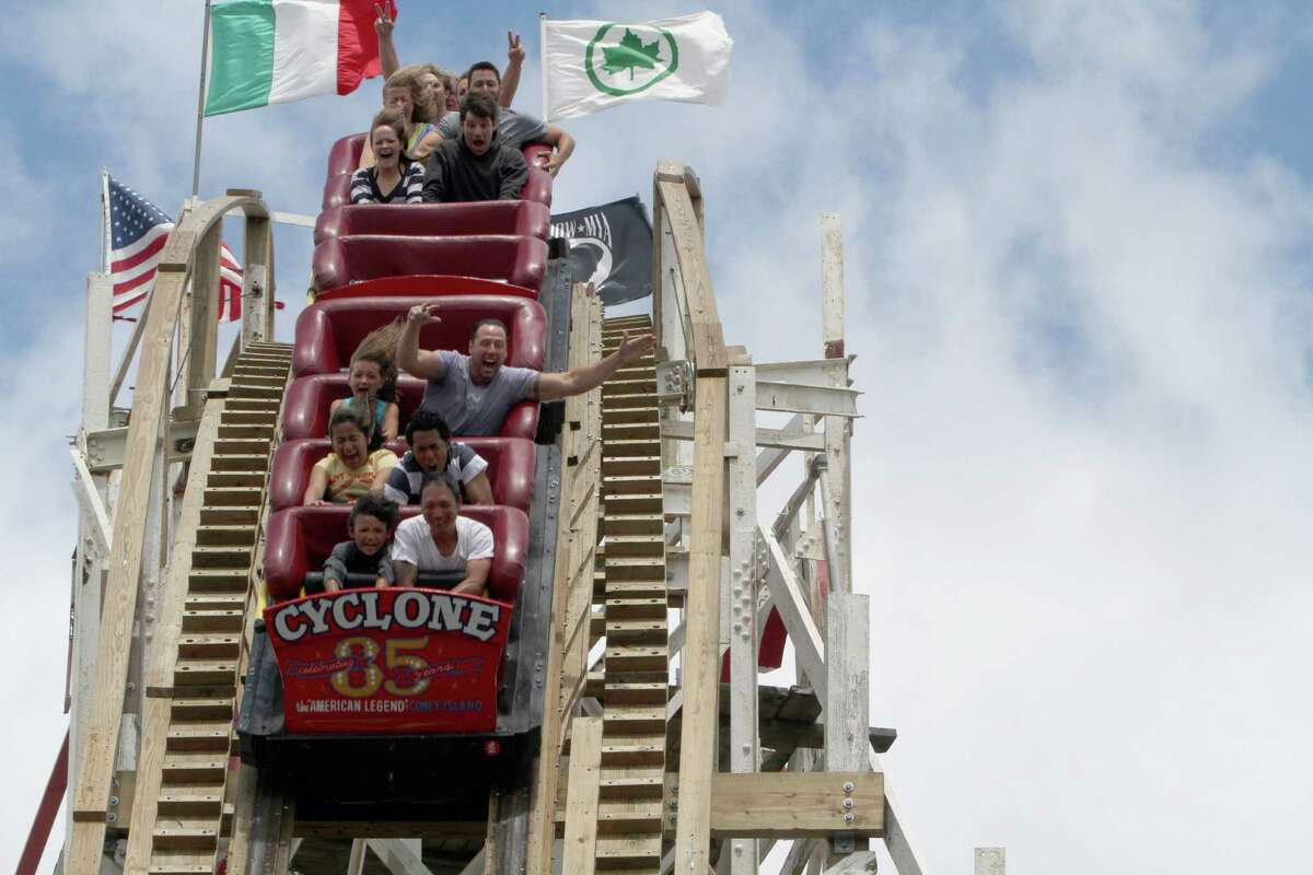 In a Tuesday, June 26, 2012 photo, people ride the Cyclone roller coaster at Coney Island in New York. The New York City landmark and international amusement icon will be feted Saturday, June 30 with a birthday party in its honor.