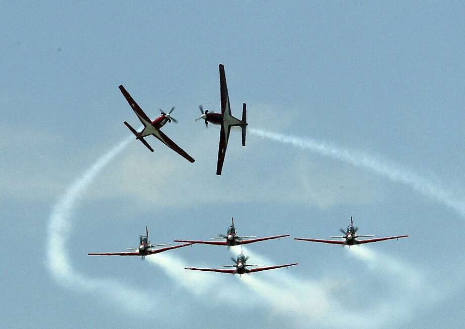 We've got to stop meeting like this: The others are watching! (Indonesian flight demonstration team Jupiter KT performing over Bangkok.) Photo: Sakchai Lalit, Associated Press