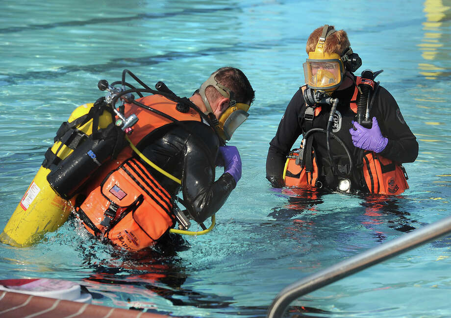 Divers prepare to scour the Magnolia Pool Friday morning for items after the body of a young man was found in the pool. The facility had also been vandalized the night before. Photo taken Friday, June 29, 2012 Guiseppe Barranco/The Enterprise Photo: Guiseppe Barranco, STAFF PHOTOGRAPHER / The Beaumont Enterprise