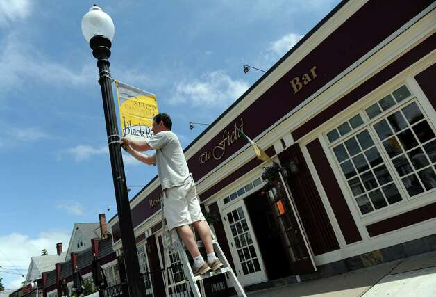 Jim Sansonetti, a member of the Black Rock Community Council, hangs banners along Fairfield Avenue in the Black Rock section of Bridgeport Saturday, June 2, 2012. Photo: Autumn Driscoll / Connecticut Post