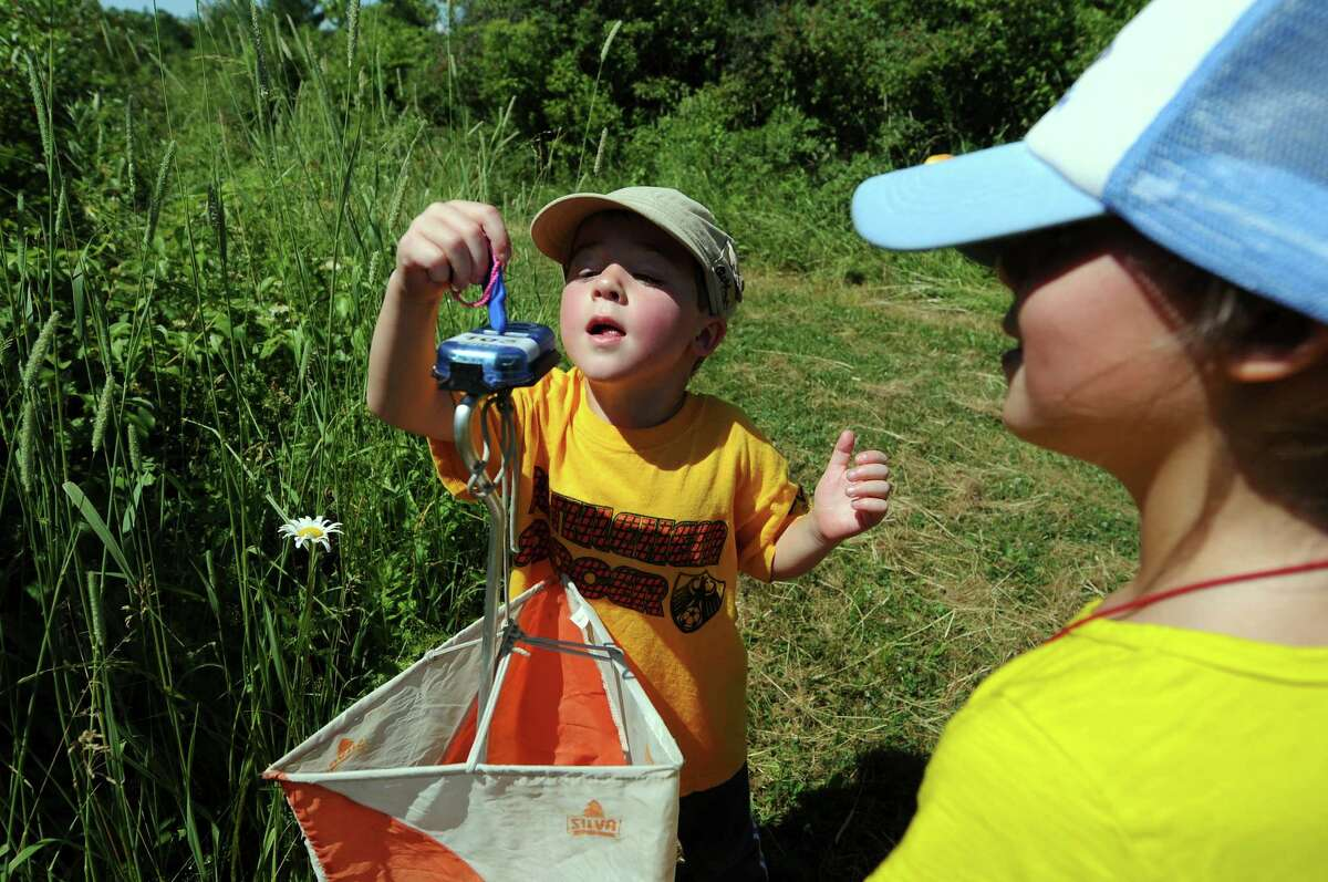 Charlie Tobin, 4, of Slingerlands, left, records a checkpoint with his sister, Lily, 7, during an orienteering event on Saturday, June 23, 2012, at Five Rivers Environmental Education Center in Delmar, N.Y. (Cindy Schultz / Times Union)