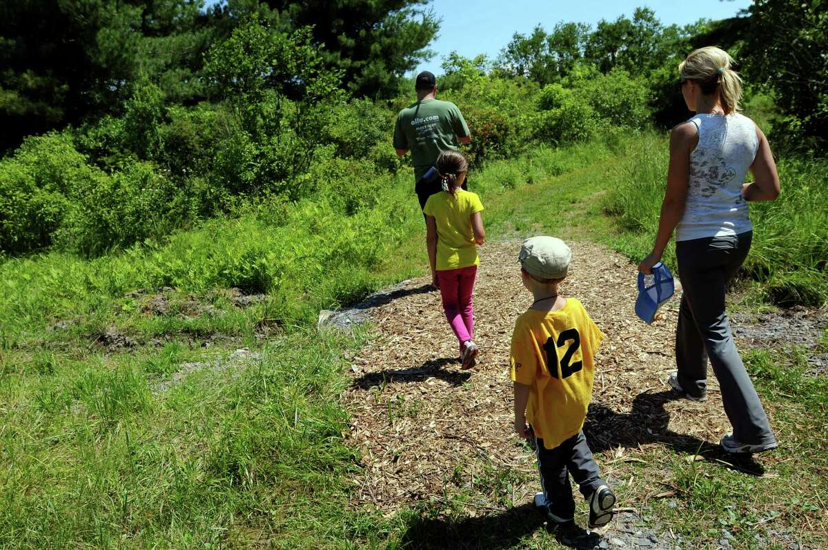 Chuck Tobin of Slingerlands, top left, leads his family through the woods during an orienteering event on Saturday, June 23, 2012, at Five Rivers Environmental Education Center in Delmar, N.Y. Joining him, from left, are daughter, Lily, 7, son Charlie, 4, and wife Andrea.