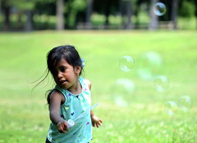 Lilyana Gomez, who turns 3 next week, waves her bubble wand through the air Friday, June 29, 2012 at Beardsley Park in Bridgeport, Conn. Photo: Autumn Driscoll / Connecticut Post