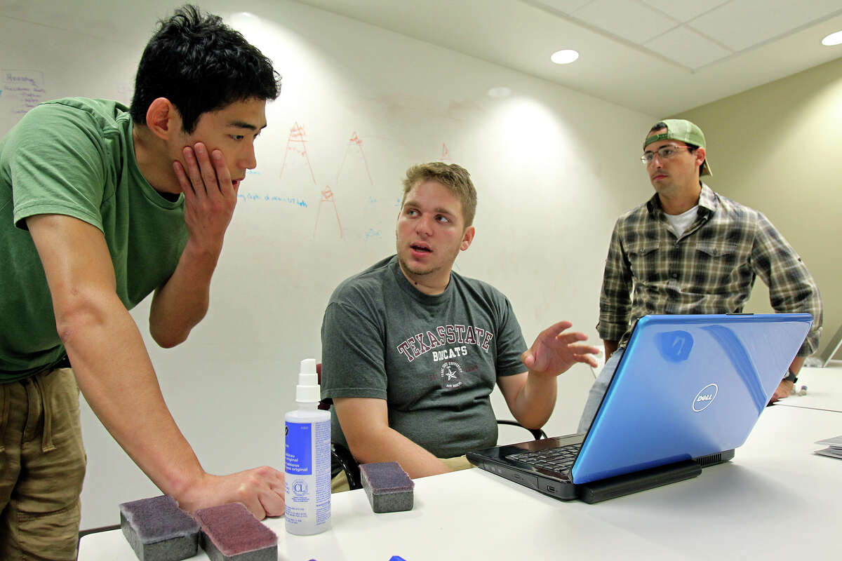 Alex Ricard (center) pitches some ideas as he works with Our Pangea co-founders Noah Simon (left) and Ari Franklin in the University of Texas Administration Building as the company goes through marketing plans on June 27, 2012.