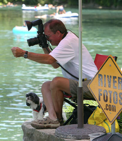 Neil Suntych makes a business of taking pictures of people tubing along the Comal River in New Braunfels. Suntych has been shooting tubers for the past three years. Tubers can see the pictures that Suntych has taken online and have the option of buying prints or digital downloads. Photo: Kin Man Hui, Kin Man Hui / Express-News / @2012 San Antonio Express-News