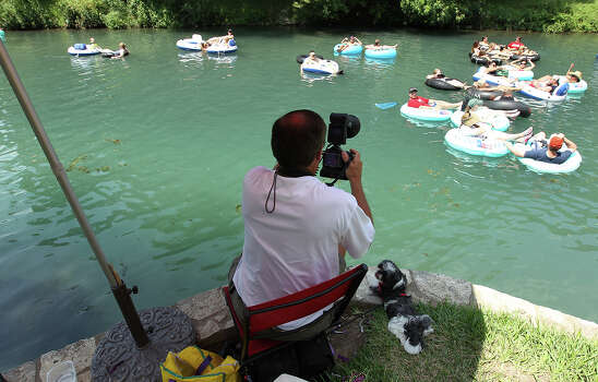 As tubers lazily float past, Neil Suntych offers to take photos as a memento on Friday, June 22, 2012. Suntych makes a business of taking pictures of people tubing along the Comal River in New Braunfels. Suntych has been shooting tubers for the past three years. Tubers can see the pictures that Suntych has taken online and have the option of buying prints or digital downloads. Photo: Kin Man Hui, Kin Man Hui / Express-News / @2012 San Antonio Express-News