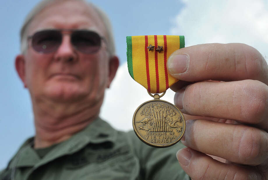 Larry McCabe holds the medal awarded to him for his service in VIetnam from 1967 to 1968.  Photo taken Thursday, June 28, 2012 Guiseppe Barranco/The Enterprise Photo: Guiseppe Barranco, STAFF PHOTOGRAPHER / The Beaumont Enterprise