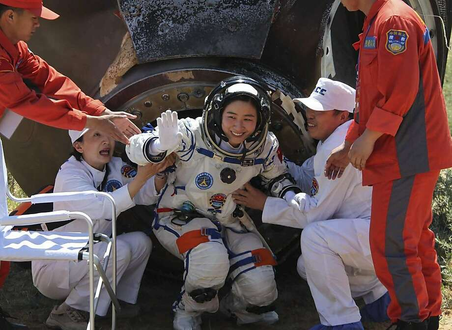 In this photo released by China's Xinhua news agency, China's first female astronaut Liu Yang waves as she comes out of the re-entry capsule of Shenzhou-9 spacecraft in Siziwang Banner of north China's Inner Mongolia Autonomous Region Friday, June 29, 2012. Liu and two other crew members emerged smiling from the capsule that returned safely to earth Friday from a 13-day mission to an orbiting module that is a prototype for a future space station. (AP Photo/Xinhua, Wang Jianmin) NO SALES Photo: Wang Jianmin, Associated Press