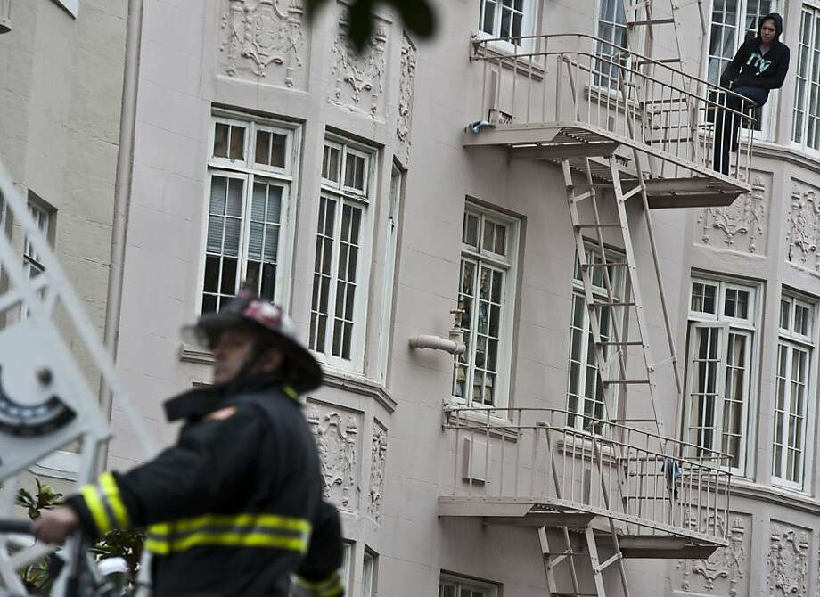 One resident watches the three-alarm fire burning at a building in San Francisco's Tenderloin neighborhood on Friday. Photo: Yue Wu, The Chronicle