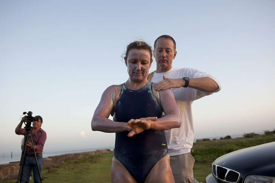 British-Australian swimmer Penny Palfrey and her husband Chris rub creme on her body in preparation for her bid to complete a record swim from Cuba to Florida, in Havana, Cuba, Friday, June 29, 2012. Palfrey aims to be the first woman to swim the Straits of Florida without the aid of a shark cage. Instead she's relying on equipment that surrounds her with an electrical field to deter the predators. (AP Photo/Ramon Espinosa) Photo: Ramon Espinosa, Associated Press
