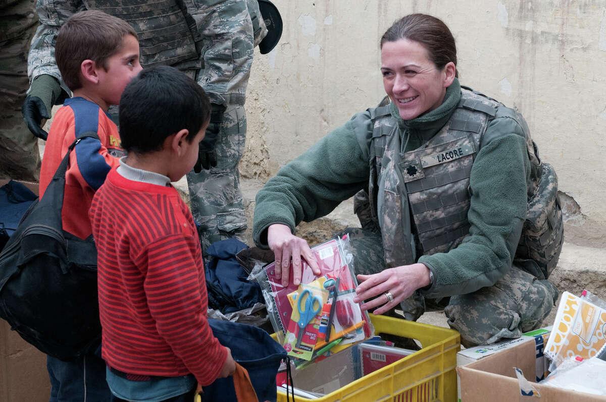 Vak Verde Christian/French Navy Navy Cmdr. Nancy Stewart Lacore helps distribute supplies to a school school in Kabul, Afghanistan.