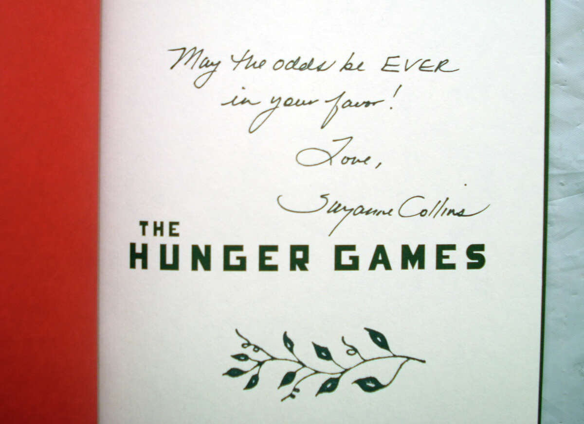 This signature and comment by author Suzanne Collins is in the first edition copy of The Hunger Games being sold at the C. H. Booth Library booksale in Newtown on July 14 ñ 18. The rare book has an asking price of $2,500.