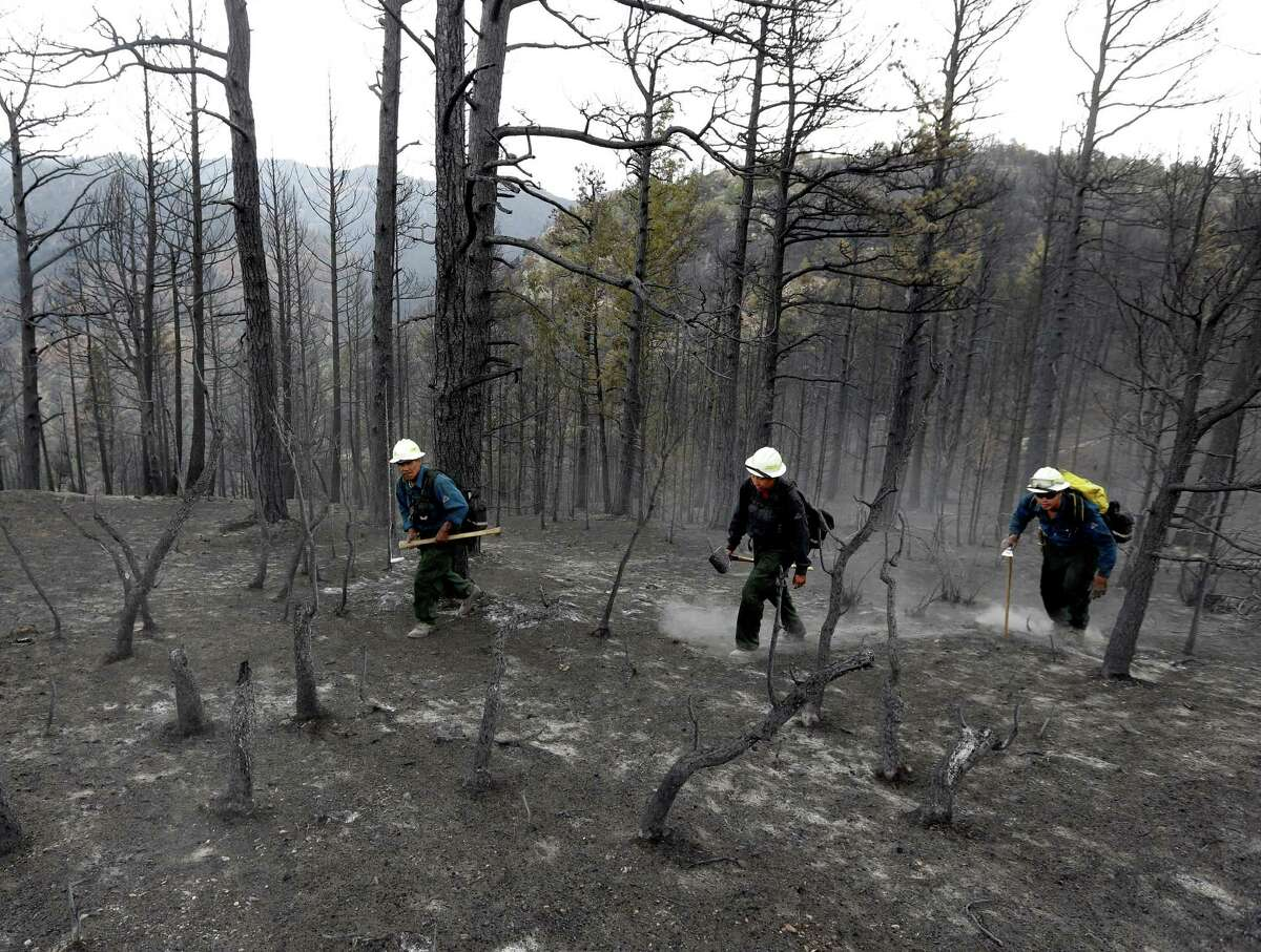Members of Bighorn 209, a hand crew from the Crow Agency in Montana check for hot spots on the Waldo Canyon Fire west of Colorado Springs, Colo., Friday, June 29, 2012. After declaring a