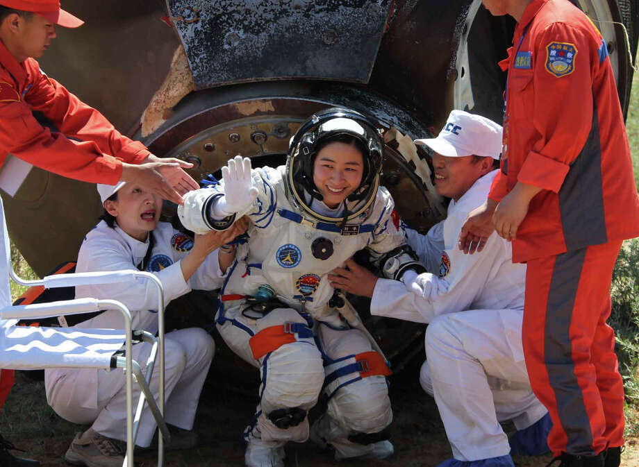 China's first female astronaut Liu Yang waves as she comes out of the re-entry capsule of Shenzhou-9 spacecraft in Siziwang Banner of north China's Inner Mongolia Autonomous Region Friday, June 29, 2012.  Photo: Wang Jianmin, Associated Press / Xinhua