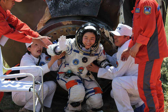 China's first female astronaut Liu Yang waves as she comes out of the re-entry capsule of Shenzhou-9 spacecraft in Siziwang Banner of north China's Inner Mongolia Autonomous Region Friday, June 29, 2012. Liu and two other crew members emerged smiling from the capsule that returned safely to earth Friday from a 13-day mission to an orbiting module that is a prototype for a future space station.