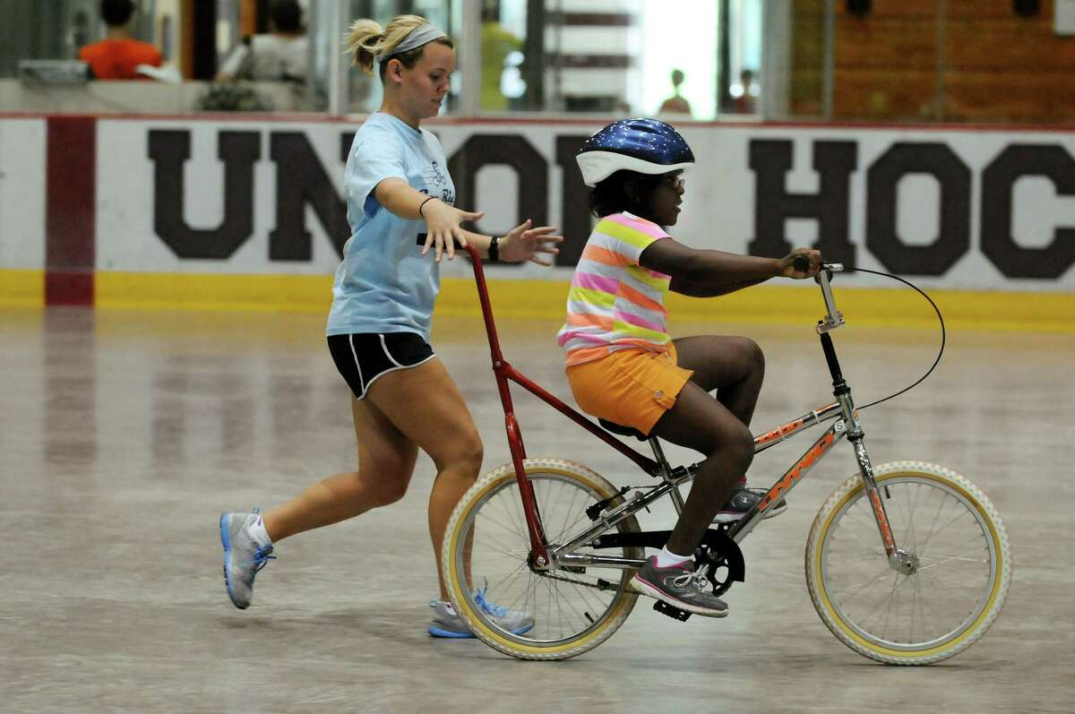 Genna Noel of Loose the Training Wheels, left, stays close as Denaezia Henderson, 8, of Schenectady learns to ride a bicycle on Thursday, June 28, 2012, at Union College in Schenectady, N.Y. STRIDE Adaptive Sports sponsors the event to teach children with disabilities how to bike ride. (Cindy Schultz / Times Union)