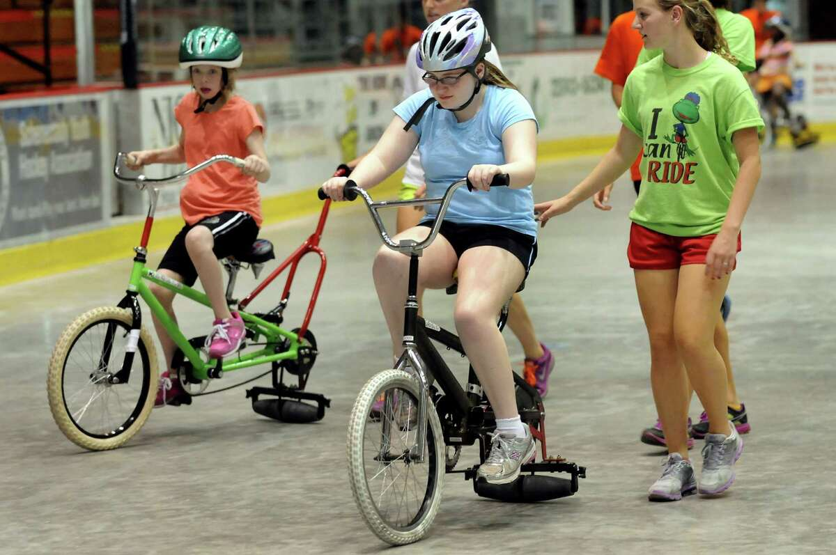 Theresa Osborne, 14, of Schenectady, left, and Julia Huber, 14, of Delmar learn to ride a bicycles on Thursday, June 28, 2012, at Union College in Schenectady, N.Y. At right is volunteer Julia Goyette, 17. Loose the Training Wheels puts on the weeklong camp to teach children with disabilities how to bike ride. STRIDE Adaptive Sports sponsors the event. (Cindy Schultz / Times Union)