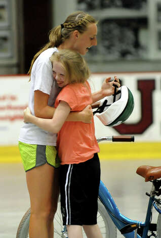 Theresa Osborne, 14, of Schenectady, right, hugs volunteer Megan McGillycuddy, 17, during a bicycle-riding camp on Thursday, June 28, 2012, at Union College in Schenectady, N.Y. Loose the Training Wheels puts on the weeklong camp to teach children with disabilities how to bike ride. STRIDE Adaptive Sports sponsors the event. (Cindy Schultz / Times Union) Photo: Cindy Schultz / 00018252A