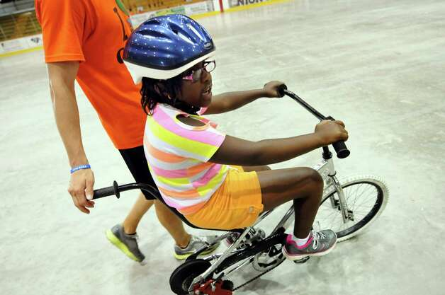 Denaezia Henderson, 8, of Schenectady circles the indoor rink during a bicycle-riding camp on Thursday, June 28, 2012, at Union College in Schenectady, N.Y. Loose the Training Wheels puts on the weeklong camp to teach children with disabilities how to bike ride. STRIDE Adaptive Sports sponsors the event. (Cindy Schultz / Times Union) Photo: Cindy Schultz / 00018252A