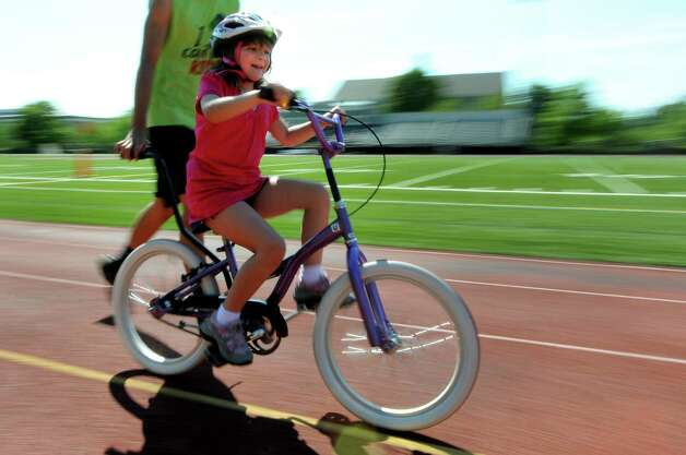 Jenna Florio, 9 of Rotterdam gets outside to ride on the track during a bicycle-riding camp on Thursday, June 28, 2012, at Union College in Schenectady, N.Y. Loose the Training Wheels puts on the weeklong camp to teach children with disabilities how to bike ride. STRIDE Adaptive Sports sponsors the event. (Cindy Schultz / Times Union) Photo: Cindy Schultz / 00018252A