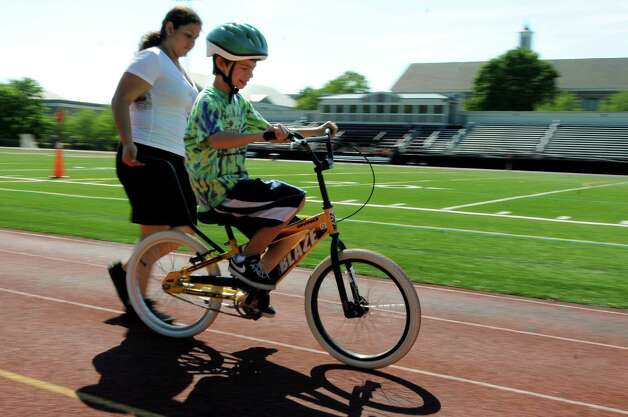 Regan Perella, 11, of Ballston Spa gets outside to ride on the track during a bicycle-riding camp on Thursday, June 28, 2012, at Union College in Schenectady, N.Y. Loose the Training Wheels puts on the weeklong camp to teach children with disabilities how to bike ride. STRIDE Adaptive Sports sponsors the event. (Cindy Schultz / Times Union) Photo: Cindy Schultz / 00018252A