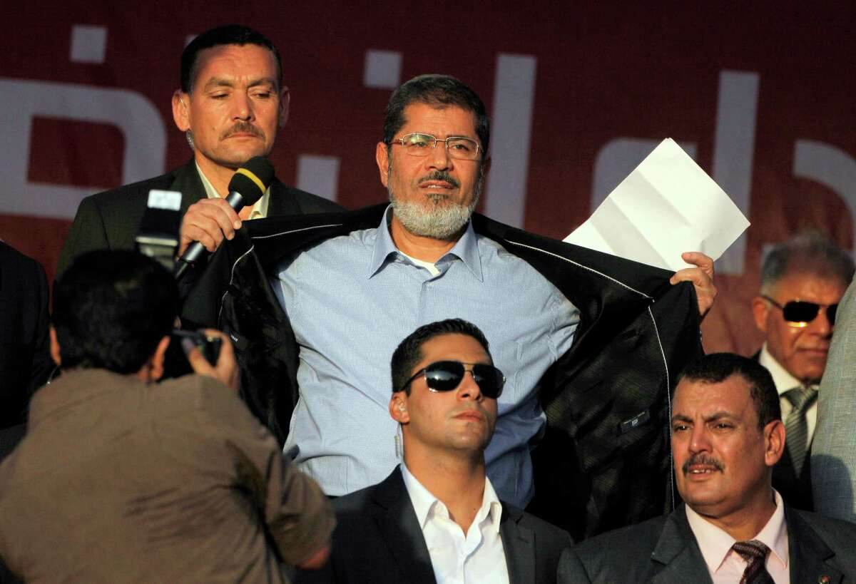 Egypt's President-elect Mohammed Morsi opens his suit jacket to show to his supporters that he is not wearing body armor at Tahrir Square, the focal point of Egyptian uprising, during his speech in Cairo, Egypt, Friday, June 29, 2012. Egypt's newly elected president has read that oath of office in Tahrir Square packed with tens of thousands of Islamists chanting against the ruling military council. In a strong-worded speech that meant to assuage popular anger at the military generals, Morsi showed defiance attempts to chip away from his own presidential powers. (AP Photo/Amr Nabil)