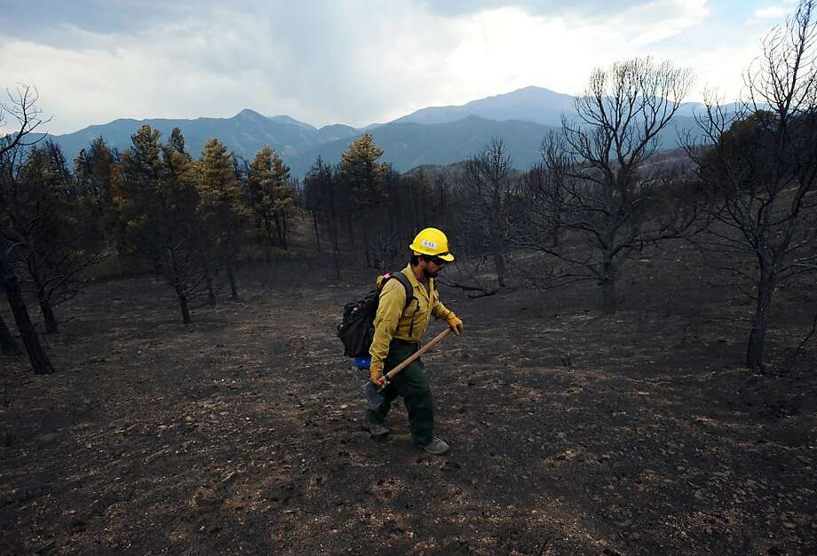"A firefighter from King Canyon National Park in California walks through a burned-out area of Colorado Springs, Colo., Friday, June 29, 2012. After declaring a ""major disaster"" in the state early Friday and promising federal aid, President Barack Obama got a firsthand view of the wildfires and their toll on residential communities. More than 30,000 people have been evacuated in what is now the most destructive wildfire in state history. (AP Photo/The Gazette, Christian Murdock) Photo: Christian Murdock, Associated Press"