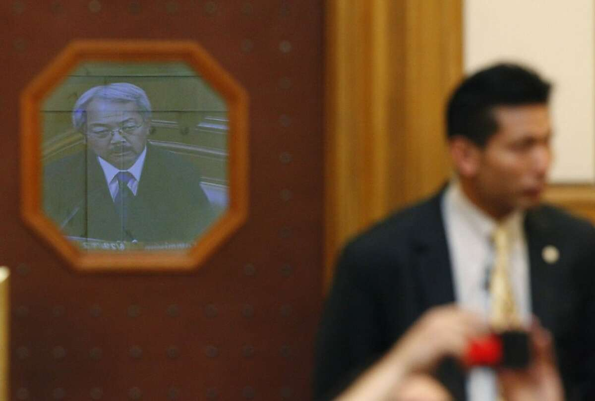 The image of Mayor Ed Lee on a television screen is reflected in a door window as he testifies before the Ethics Commission during suspended Sheriff Ross Mirkarimi's official misconduct hearing at City Hall on Friday, June 29, 2012 in San Francisco, Calif.