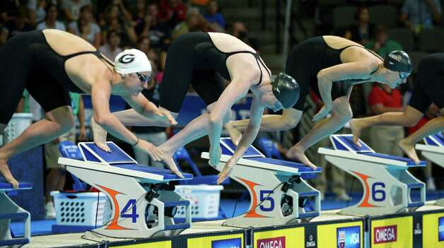 Megan Romano, from left, Missy Franklin and Allison Schmitt dive at the start of a heat in the women's 100-meter freestyle preliminaries at the U.S. Olympic swimming trials, Friday, June 29, 2012, in Omaha, Neb. (AP Photo/Mark J. Terrill) Photo: Associated Press
