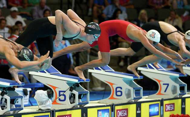 Allison Schmitt and Margo Geer, right, dive at the start of a women's 100-meter freestyle semifinal at the U.S. Olympic swimming trials, Friday, June 29, 2012, in Omaha, Neb. (AP Photo/Mark J. Terrill) Photo: Associated Press