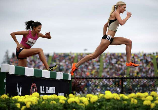 Emma Coburn, right, leads Delilah DiCrescenzo over the water jump in the women's 3000 meter steeplechase final at the U.S. Olympic Track and Field Trials Friday, June 29, 2012, in Eugene, Ore. Emma Coburn finished first.  (AP Photo/Matt Slocum) Photo: Associated Press