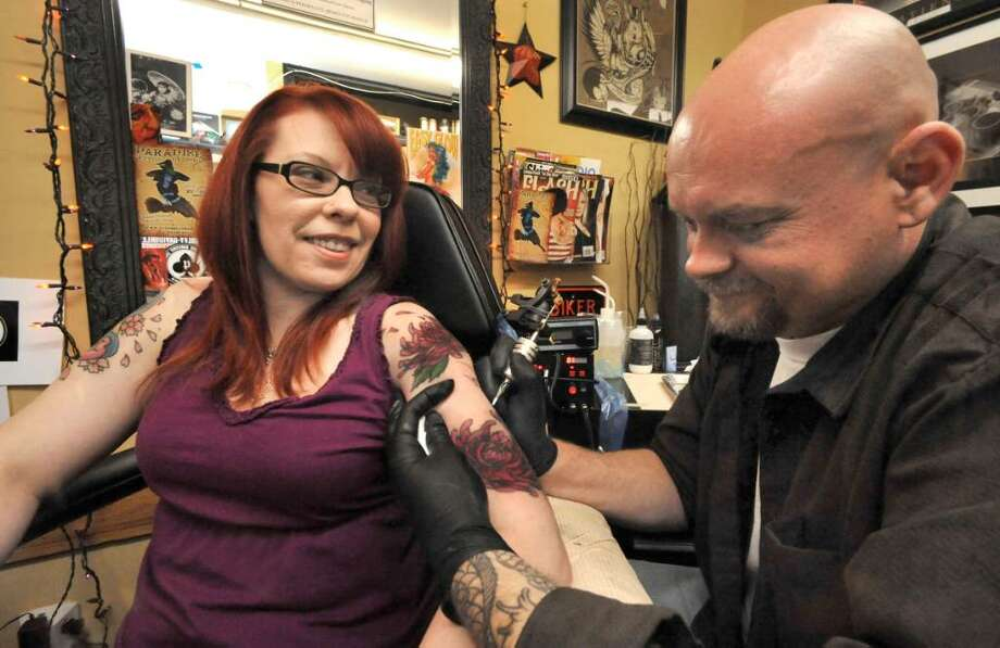 Kat Bradbury, of Bethel, recieves a continuation of a traditional Japanese half sleeve tattoo from Paul Greiser, at Peter Tat-2, in Danbury, on Saturday, Nov.7,2009. Photo: Michael Duffy / The News-Times
