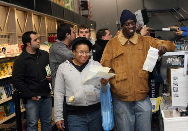 Black Friday shoppers, Leslie McKinney, left and Bobby Jones, both of Waterbury, wait in line holding vouchers for computers and video games inside Best Buy in Trumbull on Friday, Nov.28, 2009. They started their wait outside the store at 7pm Thursday. McKinney  was able to get everything she hoped for in holiday gifts for her children. Photo: B.K. Angeletti / Connecticut Post