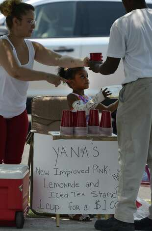 "Yana Coleman 5, watches her mom Theresa Mazera, left serve some of the ""New Improved Pink Lemonade and Iced Tea"" to Mark Reed who stopped after he left work to get some refreshment at Yana's street side stand in Albany, N.Y. June 29, 2012.  (Skip Dickstein/Times Union) Photo: Skip Dickstein"