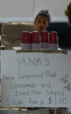 "Yana Coleman 5, looks for customers for some of the ""New Improved Pink Lemonade and Iced Tea"" at her street side stand in Albany, N.Y. June 29, 2012.  (Skip Dickstein/Times Union) Photo: Skip Dickstein"