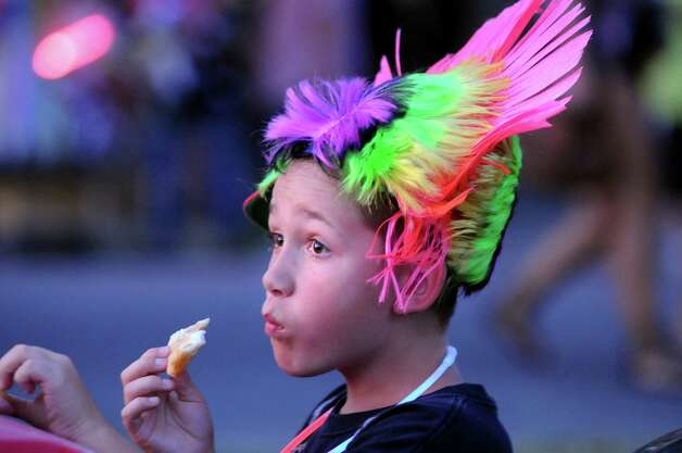 Brandon Kress, 11, of Scotia wears his new mohawk wig and eats fried dough as he waits for the fireworks show to start on Friday, June 29, 2012, at Freedom Park in Scotia, N.Y. (Cindy Schultz / Times Union) Photo: Cindy Schultz / 00018293A