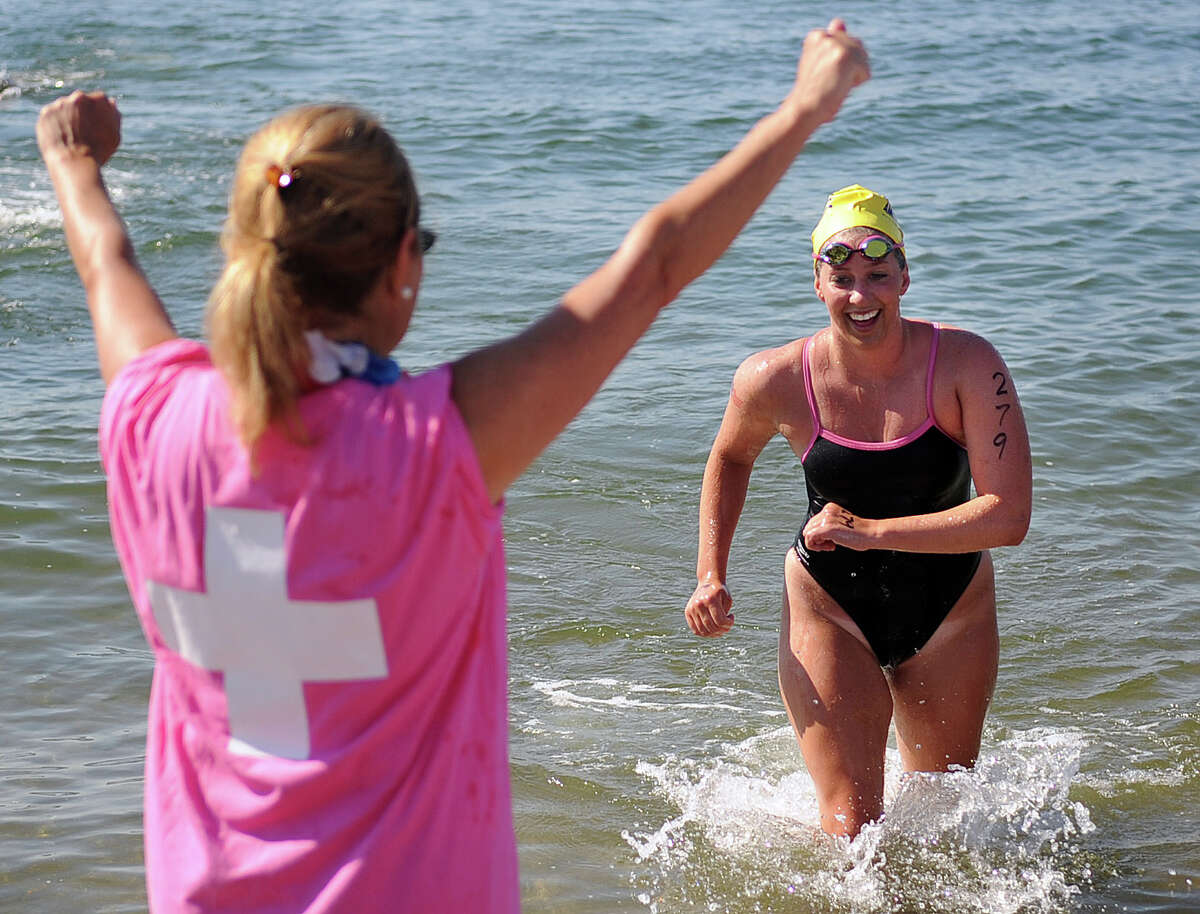 A volunteer on land raises her arms in celebration as swimmer Brooke Lorenz finishes the 1.5-mile course during Saturday's Swim Across America event off Cummings Point Road in Stamford on June 30, 2012. Lorenz was diagnosed with Hodgkin's Lymphoma when she was 17-years-old.