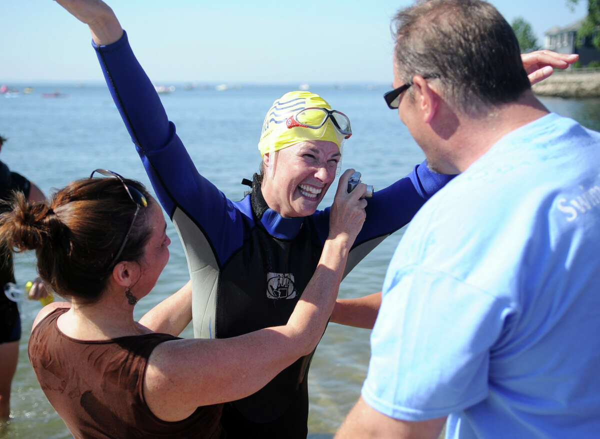 Tina Weiss is congratulated after finishing the 1.5-mile course during Saturday's Swim Across America event off Cummings Point Road in Stamford on June 30, 2012. The event raises money for cancer research.