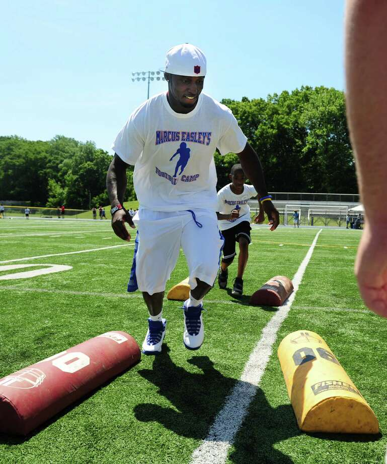 Former Husky and current Buffalo Bills wide receiver Marcus Easley runs through a drill during his 2nd Annual E.A.S.Y (Excellence, Achievement, Striving, Youthful) Summer Camp, a one-day football camp for children 6-15 years old, at Bunnell High School in Stratford Saturday, June 30, 2012. Photo: Autumn Driscoll / Connecticut Post